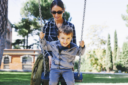 Mother pushing son on a swing at the playground - EBSF001002