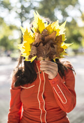 Woman covering her face with autumn leaves - DEGF000570
