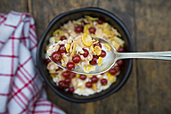Bowl of yogurt with cornflakes and red currants, spoon - LVF004087