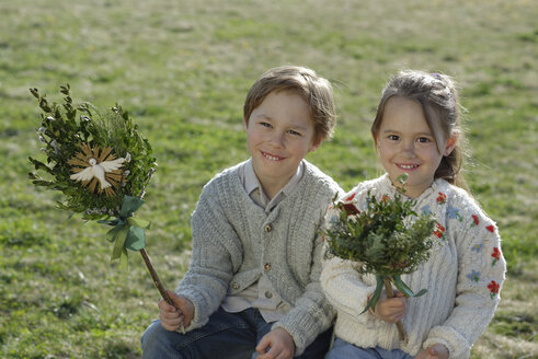 Germany, Upper Bavaria, little boy and girl with Palmbusch on a meadow - LBF001269