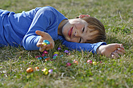 Smiling boy lying on a meadow with many chocolate eggs - LBF001275