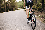 Cyclist riding a racing cycle on a road - JRFF000157