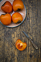 Whole and sliced kaki persimmons and a kitchen knife - LVF004101