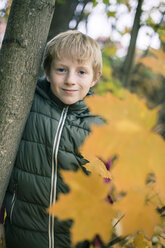 Portrait of smiling boy leaning against tree trunk in autumn - SARF002259