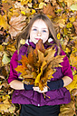 Portrait of girl lying on the ground holding bunch of autumn leaves - SARF002265