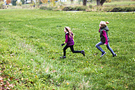 Boy and girl running over a meadow - SARF002268