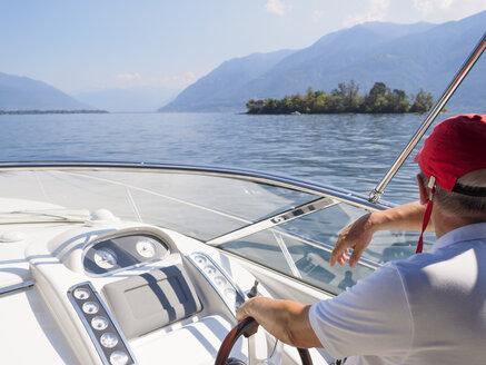 Switzerland, Ticino, Lago Maggiore, senior man on boat - LAF001527