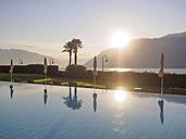 Switzerland, Ticino, Lago Maggiore, swimming pool at lakeside - LAF001533