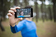 Selfie of a runner on the display of a smartphone - RAEF000607