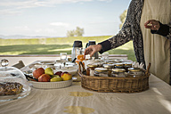 Italy, Tuscany, Maremma, woman at laid breakfast table on terrace - RIBF000340