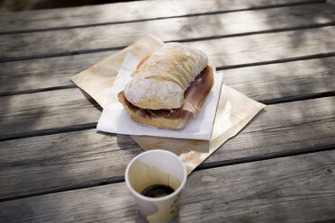 Ciabatta with Parma ham on wooden table outdoors - RIBF000358