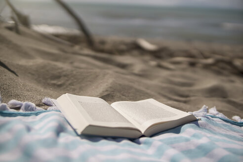 Italy, Tuscany, Maremma, book on beach towel - RIBF000367