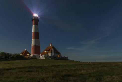 Germany, Schleswig-Holstein, North Sea Coast, View of Westerheversand Lighthouse at night - KEB000266