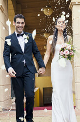 Bridal couple after the wedding under rain of rose petals and rice grains - GEMF000460