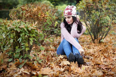 Young woman wearing autumn fashion sitting on the ground covered with autumn leaves - GDF000893