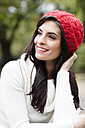 Portrait of smiling young woman wearing red woolly hat - GDF000896