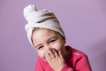 Portrait of laughing little girl covering  mouth with her hands wearing towel turban - ERLF000068