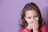 Portrait of laughing little girl covering mouth with her hands - ERLF000076