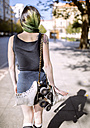 Spain, Gijon, back view of young woman with green dyed hair carrying inline skates over shoulder - MGOF000981