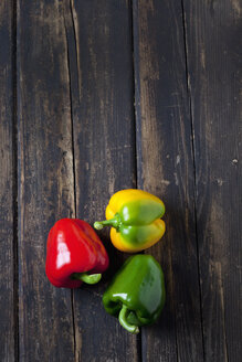 Red, yellow and green bell pepper  on dark wood - CSF026633