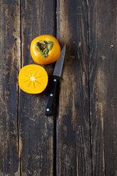 Whole and sliced kaki and a knife on dark wood - CSF026636