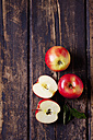 Whole and sliced red apples on dark wood - CSF026645
