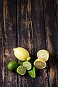 Whole and sliced lemons and limes  on dark wood - CSF026648