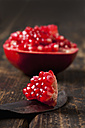Piece of sliced pomegranate on knife blade and dark wood - CSF026678