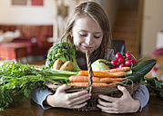 Portrait of smiling girl with wickerbasket of fresh vegetables at home - SARF002277