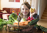 Portrait of grinning girl with wickerbasket of fresh vegetables at home - SARF002280