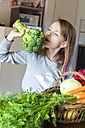 Portrait of singing girl using broccoli as a microphone - SARF002283