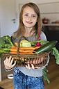 Portrait of smiling girl holding wickerbasket of fresh vegetables - SARF002286