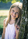 Portrait of smiling little girl leaning against tree trunk - SARF002289