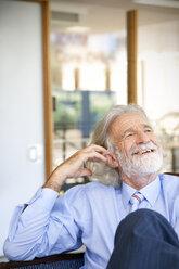 Laughing senior man sitting in chair, portrait - RMAF000182