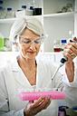 Female professor filling sample glasses in laoratory - RMAF000188