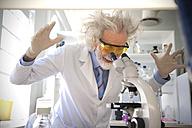 Tousled professor examining samples under microscope, looking surprised - RMAF000191