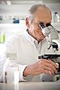 Professor in laboratory examining samples under microscope - RMAF000194