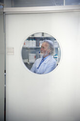 Senior professor looking through window of laboratory door - RMAF000197