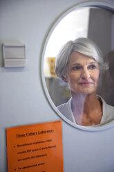 Senior woman looking through window of laboratory door - RMAF000200