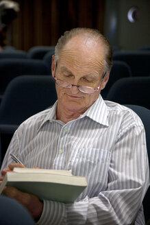 Senior with textbook studying at university - RMAF000206