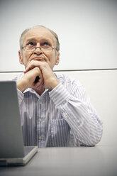 Senior man sitting in office using laptop - RMAF000209