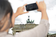 Germany, Berlin, young tourist photographing Brandenburger Tor with smartphone - BFRF001600