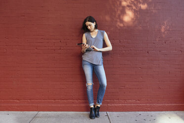 Portrait of woman with digital tablet leaning against red brick wall - GIOF000384
