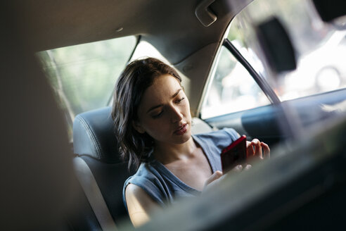 Portrait of young woman sitting  inside of a cab using her smartphone - GIOF000405