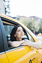 USA, New York City, portrait of smiling young woman looking through window of a yellow cab - GIOF000408