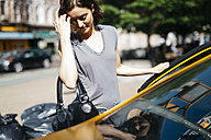 USA, New York City, young woman getting on a yellow cab - GIOF000411