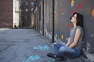 USA, New York City, young woman sitting on the ground leaning against a wall - GIOF000414