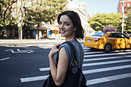 USA, New York City, Manhattan, portrait of smiling young woman crossing a street - GIOF000420