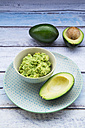 Bowl of Guacamole and whole and sliced avocados on light blue wood - LVF004109