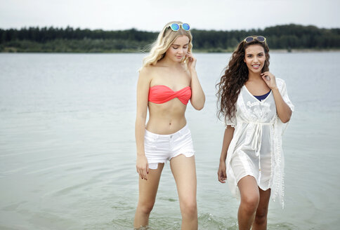 Germany, Haltern, two young women wading through water of Silbersee - GDF000902